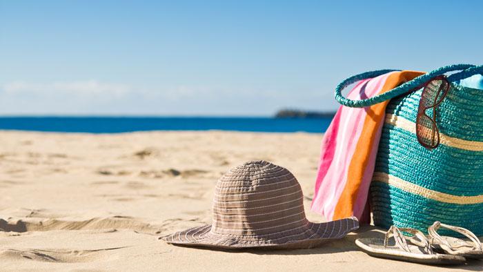 Beach bag and hat lying on the beach