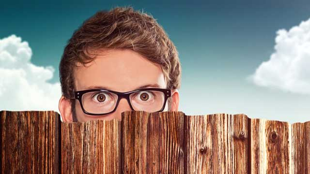 Man with Glasses Peeking over Wooden Fence