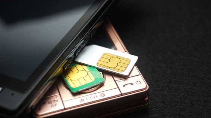 2 SIM cards under smartphone on black background