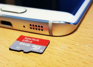 64 GB SD Card near smartphone on desk