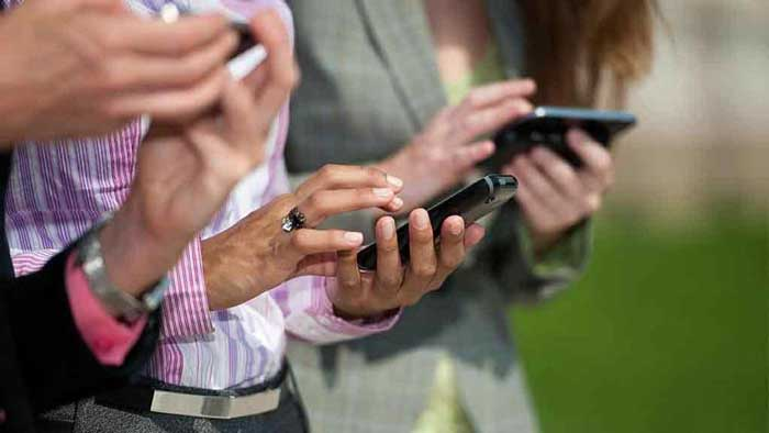3 people's standing near each other on their devices