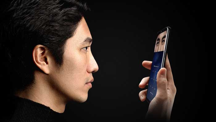 Man Staring into Smartphone Iris Scanner with Black Background