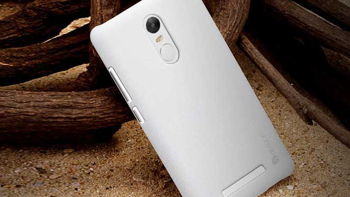 Smartphones with white back in the sand leaning against a tree
