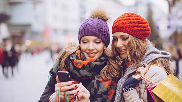 Two women glancing at same smartphone dressed warmly