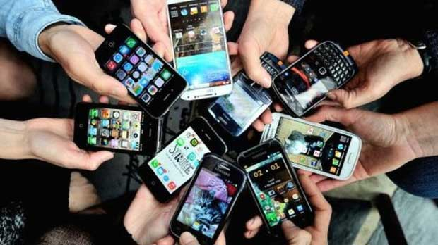 Many peoples hands holding mobile devices