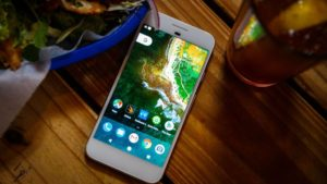 Google Pixel on wooden table near food and drink