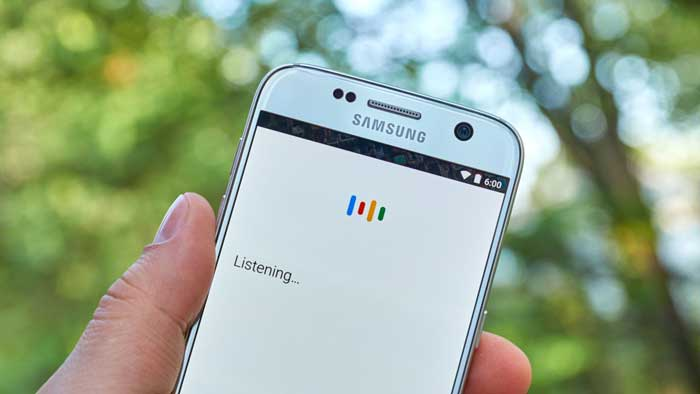 Samsung Smartphone open to OK Google blurred trees behind
