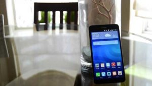 Huawei Ascend XT lying on glass vase on table