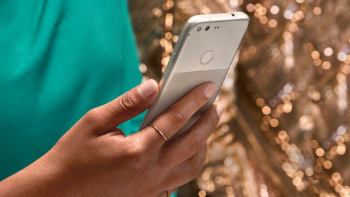 Hand wearing ring holding white google pixel 2