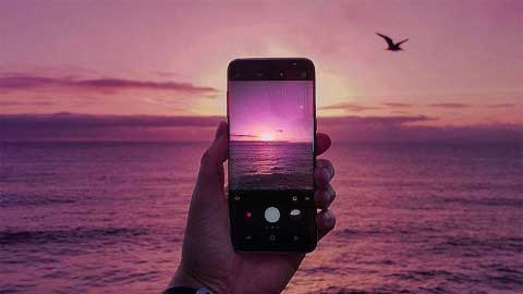 Hand holding Samsung S8 taking image of Sunset over water
