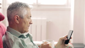 Older man sitting on red couch on his smartphone