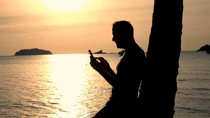 Man on his phone in the shadow of sunset