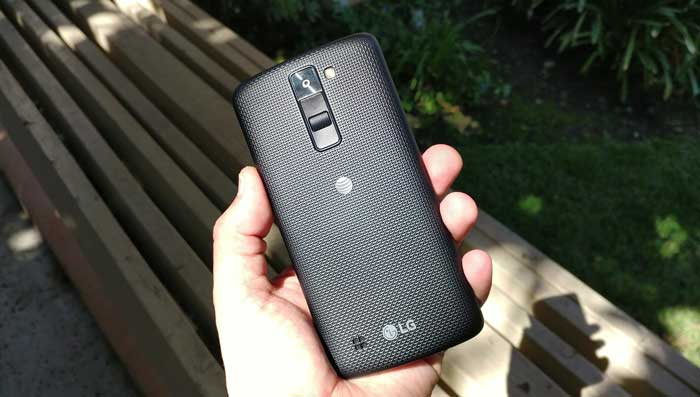 LG K8 Phoenix 2 being held outdoors grass bench