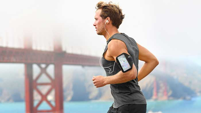 Man jogging near bridge with armband smartphone