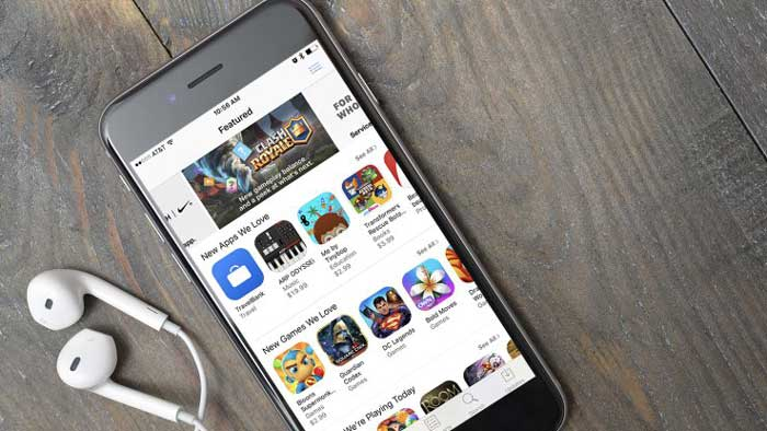 Smartphone with App store open near ear buds on wood