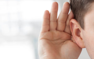 Man holding hand up to ear as if having trouble hearing