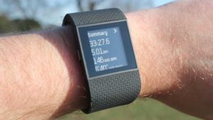 Hand wearing Fitbit Surge Fitness Tracker