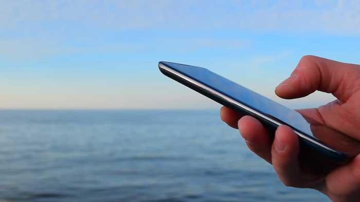 Hand holding Phone near water