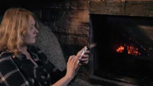 Lady near the fireplace holding her smartphone