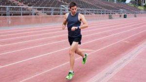 Man jogging on race track wearing fitness tracker bracelet