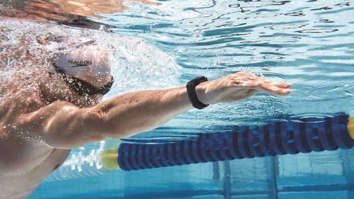 Man swimming wearing fitness racker