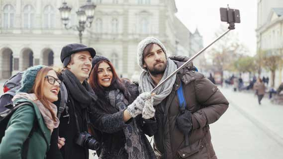 4 people taking an image using a selfie stick at landmarks