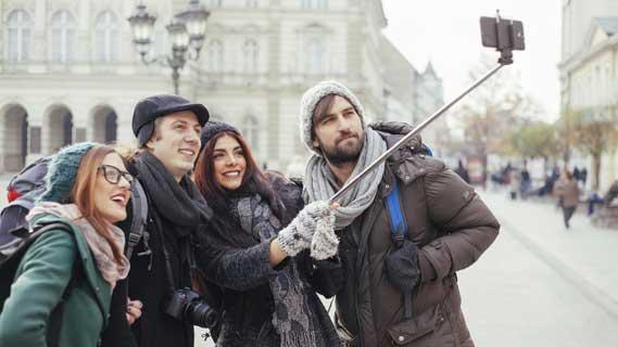 4 people taking an image using a selfie stick at landmarks