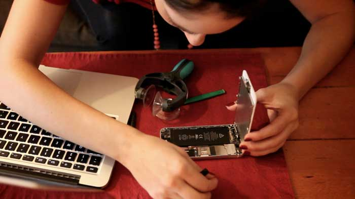 Women repairing a smartphone at her desk her near laptop