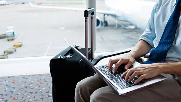 Businessman on laptop while in airport