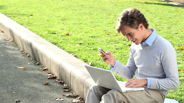Man sitting on the curb at a park while on smartphone and laptop