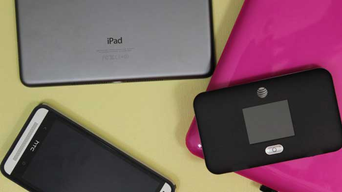 Netgear Unite Express hotspot lying on a pink laptop and near an iPad and smartphone