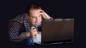Man laying on his stomach working at a laptop while frustrated