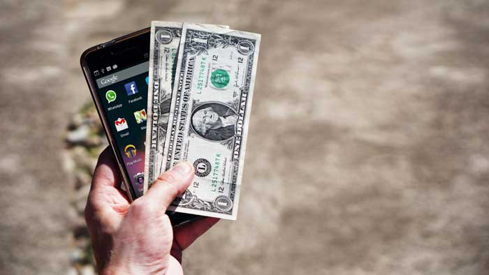 A Hand holding a smartphone along with cash outdoors