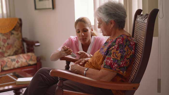 A Nurse in a Nursing Home helping an older lady with a smartphone