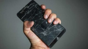 Hand gripping smartphone with broken screen