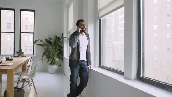 Businessman talking on cellphone near window