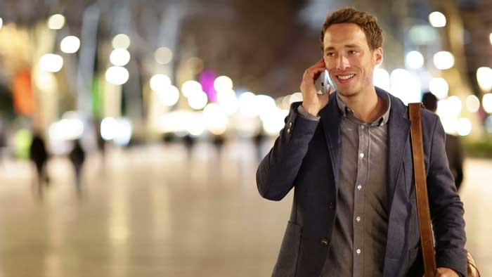 Businessman Crossing the Street while Talking on his Cell Phone