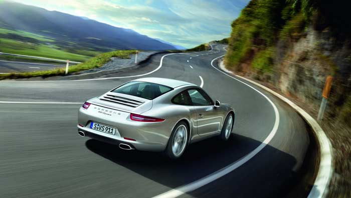 Porche driving on windy road near mountains