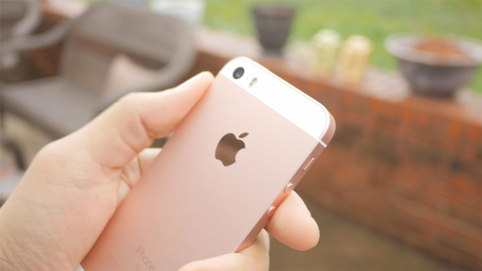 pink iPhone SE being held outdoors