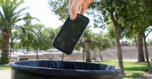 Throwing out a smartphone into the park trash bin