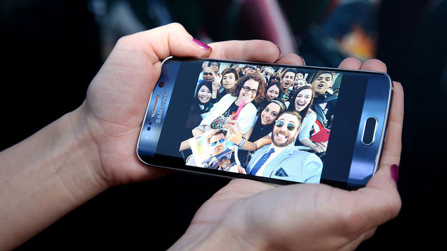 Someone's hands holding a smartphone with image of celebrity and fans taking a selfie