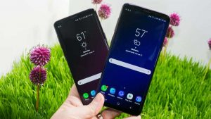 Hand holding Samsung Galaxy S9 and S9 plus in front of grass