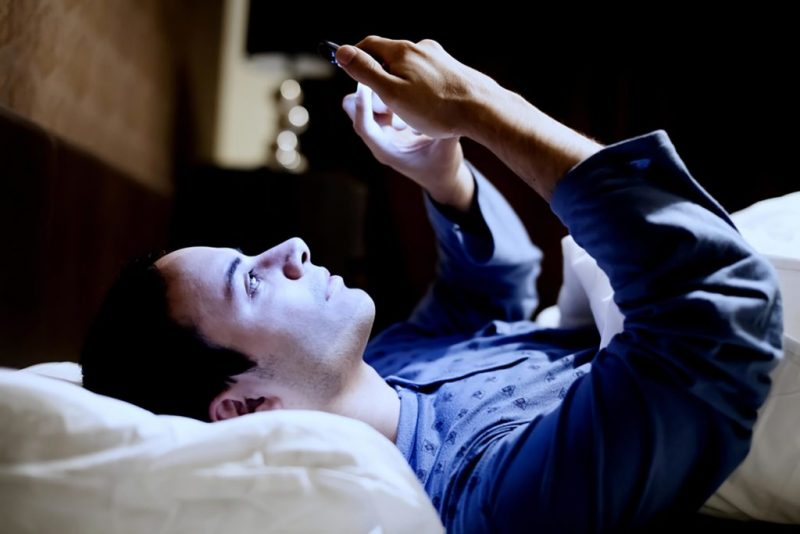 Man laying in bed on his phone with blue light emitting