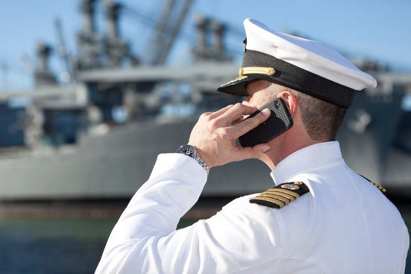 Man in uniform, a sailor, on his mobile device