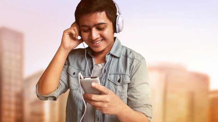 Man smiling while listening to music from smartphone