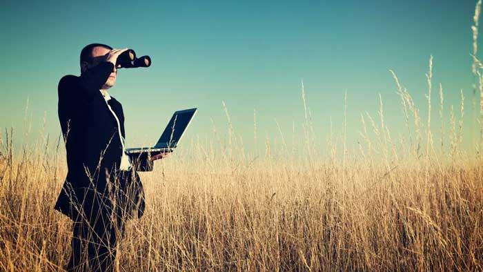 Man looking through binoculars to find someone