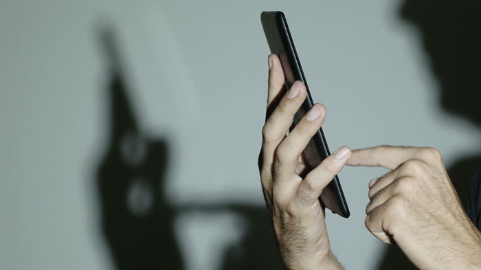 Man tapping smartphone while having a strong shadow on the wall
