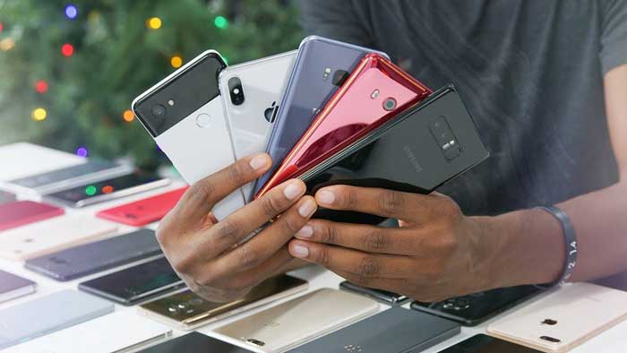 Man fanning open multiple smartphones over a table of more phones