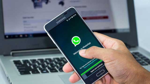 Hand holding Phone open to whatsapp app near a laptop