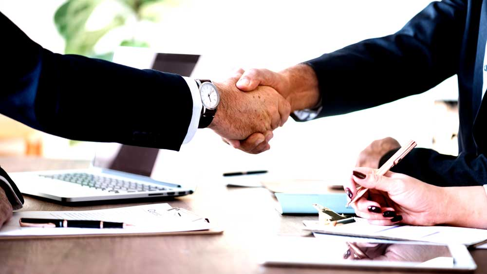 Two men shaking hands on a deal over a table